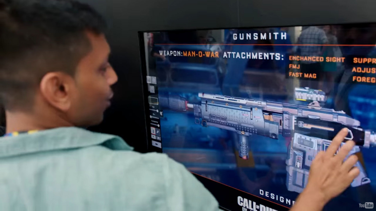 Air Graffiti Touch, Interactive Digital Surface: A participant customizing a virtual weapon using touch drawing @ a Call of Duty event